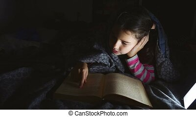 teen girl child book reading night with flashlight lying a...
