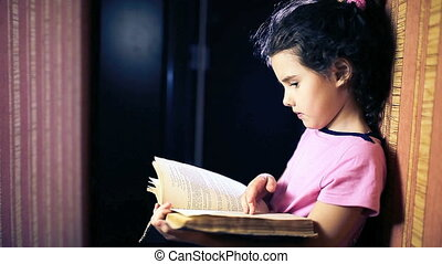 Teen girl child reading a book while standing against a wall in the apartment flipping page