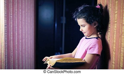 Teen girl child reading book while standing against a wall...