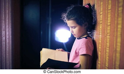 Teen girl child reading book while standing against wall in...