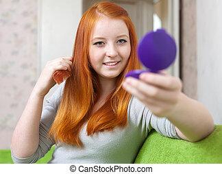 teen girl combing hair
