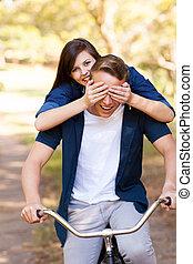 teen girl covering boyfriend's eyes with hands on bike