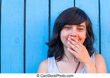 Teen girl covers her mouth with her hand, on the background of blue wooden walls.