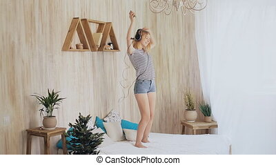 Teen girl dancing with headphones at home