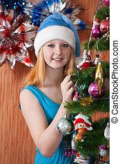 Teen girl decorates spruce