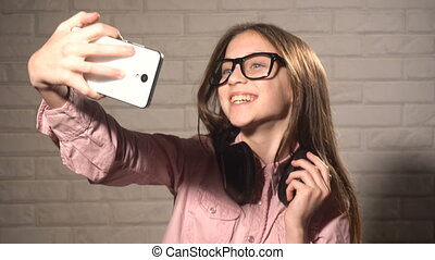 Teen girl doing selfie with herself on smartphone