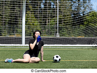 Teen girl drinking a lot of water during a hot day on the soccer field