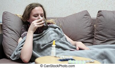 Teen girl drinking medicine tea warm. Lying on the couch, covered with a blanket