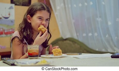 teen girl drinking the tea and eating cake, indoor lifestyle watching television tv at breakfast dinner