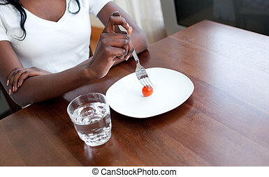 Teen girl eating a tomato. Anorexia concept.