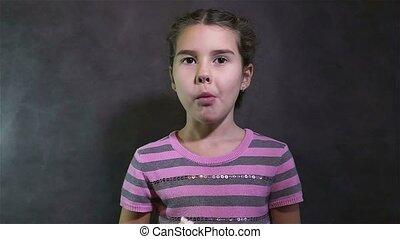 Teen girl eating crab sticks on gray background - Teen girl...
