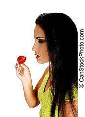 Teen girl eating strawberry.