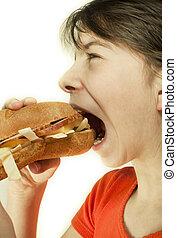 Teen girl eats a huge hamburger
