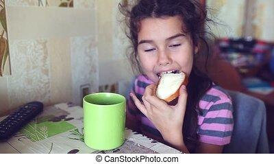 teen girl eats bread with butter tea drinkers breakfast -...
