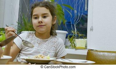 Teen girl eats food hungry lettuce at table - Teen girl eats...