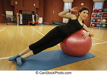 teen girl exercise with power ball in gym