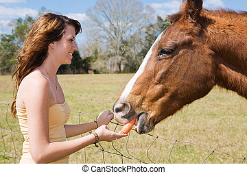 Beautiful teen girl giving a carrot to her horse.