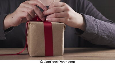 teen girl hands tying ribbon bow on present box, 4k prores ...