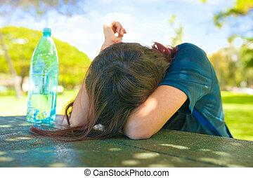 Teen girl head down on table on sunny day outdoors