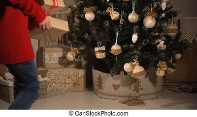 Teen girl hiding gifts under Christmas tree