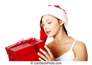 Teen girl holding and looking at gift.
