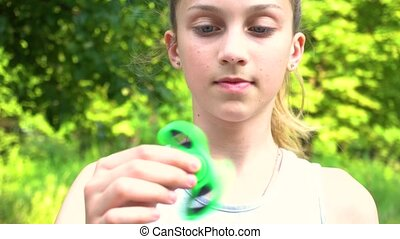 Teen girl holding and spinning green spinner in her hands....