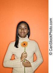 Teen girl holding flower.