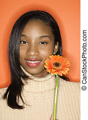 Teen girl holding flower.