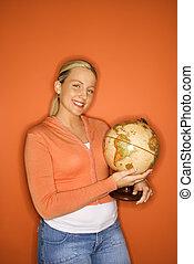 Teen girl holding globe.