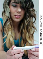 Teen girl holding pregnancy test