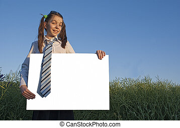 Teen girl holding white poster at green field