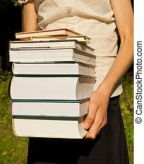 Teen girl holds a stack of books