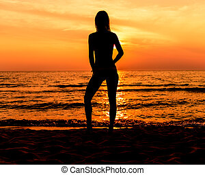 Teen Girl In A Dress With Long Hair At The Beach In Silhouette During Sunset In A Casual Pose