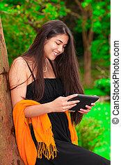 Teen girl in black dress outdoors using tablet computer