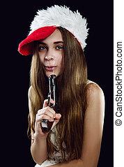 Teen girl in christmas hat with handgun