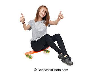 Teen girl in full length sitting on skate board