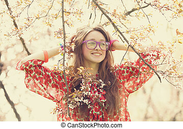 Teen girl in glasses near blossom tree