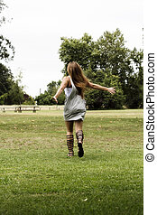 Teen Girl In Gray Dress And Sandals Running On Grass