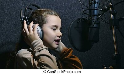 teen girl in headphones singing into microphone recording studio