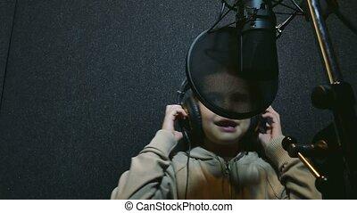 teen girl in headphones singing  into microphone professional audio studio music