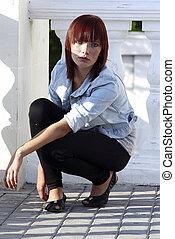 teen girl in leggings squatting on ballustrade
