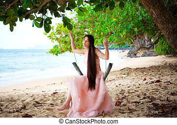 Teen girl in pink dress sitting on swing at beach