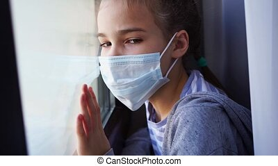 a teen girl in a protective mask, look out of the window outside. she is sick and self-isolating during the pandemic. misses her friends and parents. distance learning.