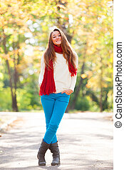 Teen girl in red scarf at autumn outdoor