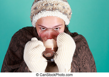 Teen girl in studio with cup of hot chocolate and winter clothes hat and mittens