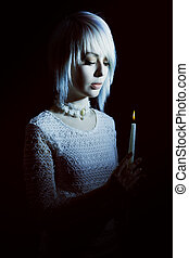 Teen girl in the dark with a candle, fear on her face