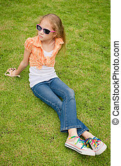 Teen girl in the park sitting on the grass.