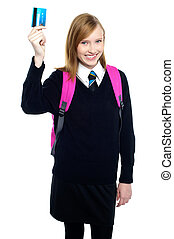 Teen girl in uniform holding up a cash card