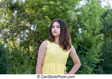 Teen girl in yellow dress standing in the park