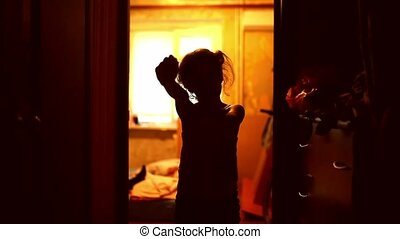 teen girl in zombie is orange silhouette stretched indoor...